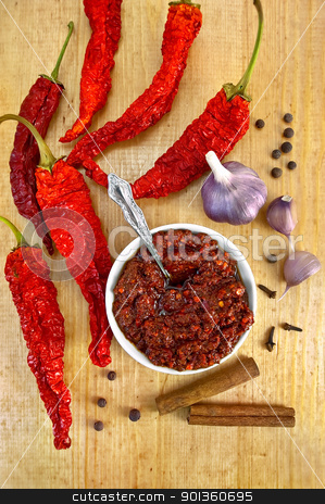 Adjika with dried hot peppers stock photo, Tabasco in a white cup with a spoon, dried red peppers, garlic, cloves, cinnamon, pea of black pepper on a wooden board by rezkrr