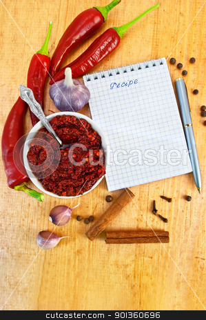 Adjika with fresh peppers stock photo, Tabasco in a white cup, fresh red peppers, garlic, cloves, cinnamon, pea black pepper, a notepad with the word recipe and a silver pen on a wooden board by rezkrr