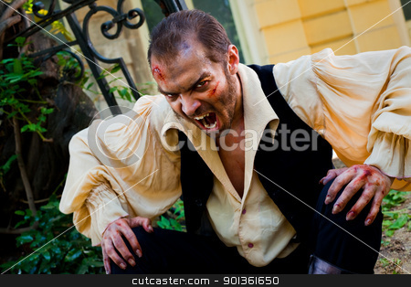 Evil male vampire stock photo, Evil male vampire with wounded face, roaring scary at camera by vilevi