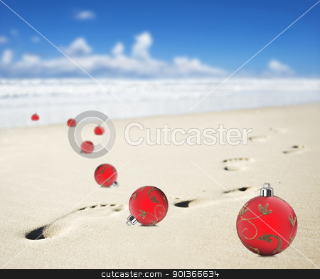 Christmas baubles on a beach with footprints stock photo, Christmas baubles on a beach with footprints by tish1