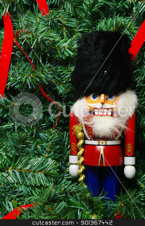 Nutcracker and a wreath  stock photo, A nutcracker against a christmas wreath with red ribbons by Ed Corey