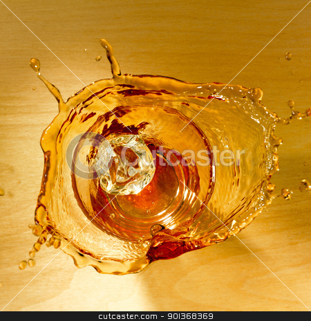 Splash of whiskey stock photo, Top shot with an icecube splashing in a glass of whiskey on a wooden background. by Han van Vonno