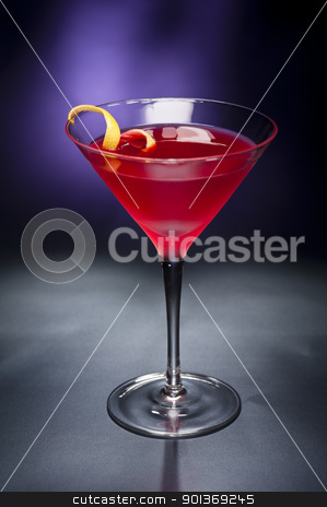 Cosmopolitan cocktail with lemon garnish stock photo, Cosmopolitan cocktail with lemon garnish in front of a black blue background by Ulrich Schade
