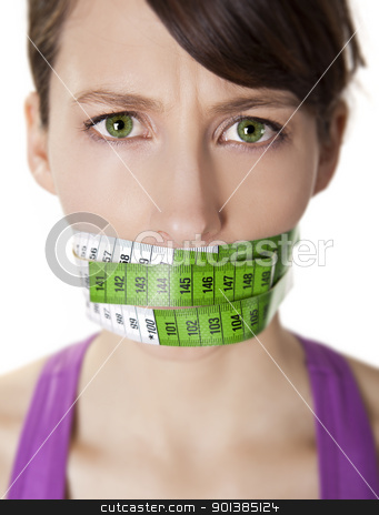 Counting calories stock photo, Portrait of a young  woman with a green measuring tape covering the mouth by ikostudio
