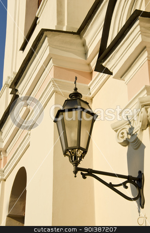 Metal illuminator on ancient wall of  building. stock photo, Metal illuminator on ancient white wall of  building. by sauletas