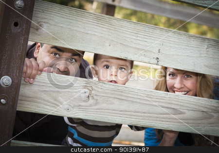 Happy Young Mixed Race Ethnic Family Looking Through Fence stock photo, Happy Young Mixed Race Ethnic Family Looking Through a fence In The Park. by Andy Dean
