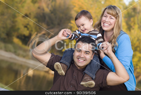 Happy Mixed Race Ethnic Family Posing for A Portrait stock photo, Happy Mixed Race Ethnic Family Posing for A Portrait in the Park. by Andy Dean