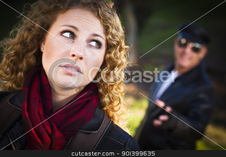 Pretty Young Teen Girl with Man Lurking Behind Her stock photo, Pretty Young Teen Girl with Mysterious Strange Man Lurking Behind Her. by Andy Dean
