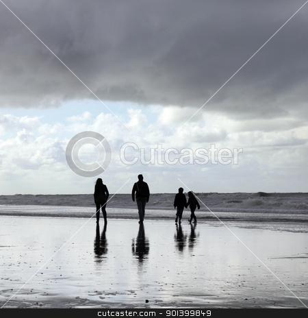 happy family strolling along beach stock photo, happy family strolling along beach and children holding hands by anton havelaar