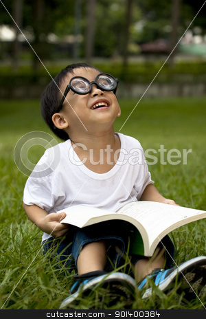 happy asian boy study on the green grass stock photo, happy asian boy study on the green grass by tomwang
