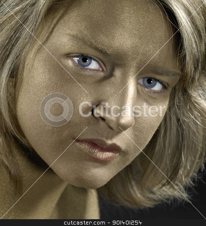 golden face of a young woman stock photo, portrait with a golden bodypainted face of a young woman with blue eyes by prill