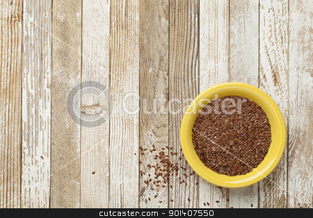 brown flax seeds stock photo, seeds of brown flux in a yellow ceramic bowl on a grunge white painted table by Marek Uliasz