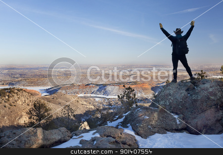 winter hiking in Colorado stock photo, silhouette of happy male hiker standing on a rock and looking down to Horsetooth Reservoir, town of Fort Collins and Colorado plains, typical hazy winter scenery by Marek Uliasz