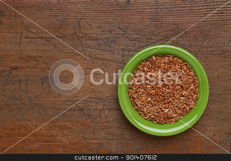 bowl of brown rice stock photo, green ceramic bowl of brown rice against weathered scratched wood background by Marek Uliasz