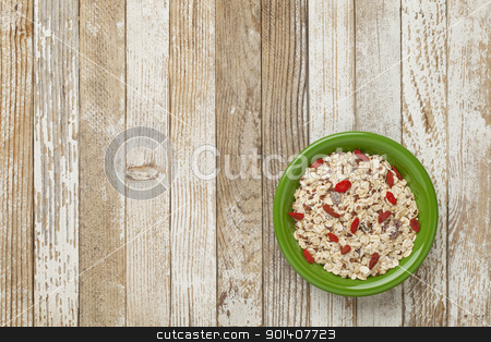 muesli cereal bowl stock photo, bowl of muesli cereal with raisins, flux seeds and goji berries against grunge wood table by Marek Uliasz