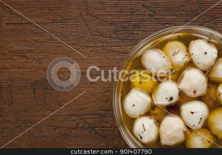 marinated mozzarella cheese stock photo, balls of mozzarella cheese marinated in oil with seasoning, glass bowl on weathered wood background by Marek Uliasz