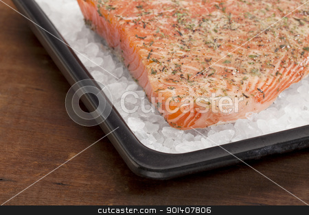 baking salmon on rock salt stock photo, a fillet of raw Norwegian salmon, seasoned with lemon juice and thyme, ready to bake on rock salt by Marek Uliasz