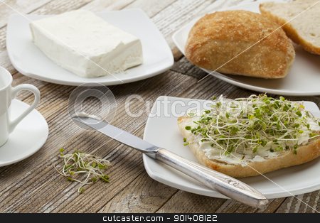 roll with cream cheese and sprouts stock photo, healthy breakfast concept - a roll with cream cheese and broccoli sprouts on a rustic wooden table by Marek Uliasz