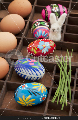 painted Easter eggs stock photo, Easter decoration concept - brown chicken eggs, painted eggs with floral motif, green chive and woolen bunny in a vintage drawer (shadow box) by Marek Uliasz