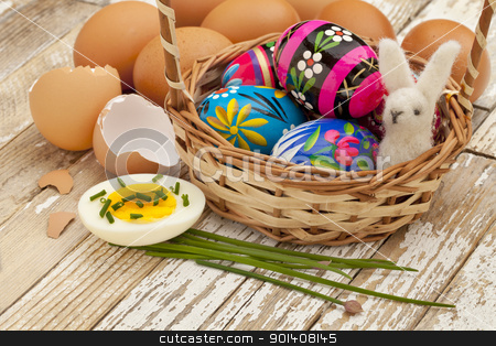 spring or Easter egg concept stock photo, Easter decoration concept - painted Easter eggs, chicken eggs with green chive and woolen bunny in a basket against grunge wooden surface by Marek Uliasz