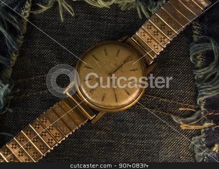 Vintage golden wristwatch. stock photo, Retro golden wristwatch close up over blue jean cloth background. by Cienpies Design