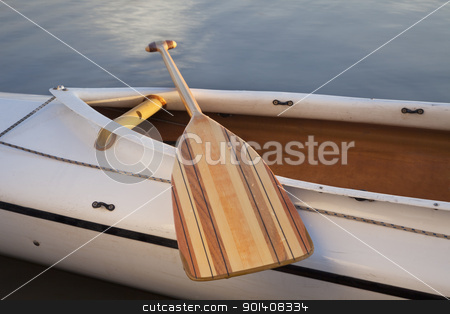 canoe paddle stock photo, a wooden paddle across cockpit of decked expedition canoe by Marek Uliasz