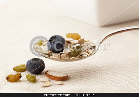 spoon of muesli cereal stock photo, spoon of muesli cereal with oats, fresh blueberries, dried golden raisins and sliced almonds, shallow depth of field by Marek Uliasz