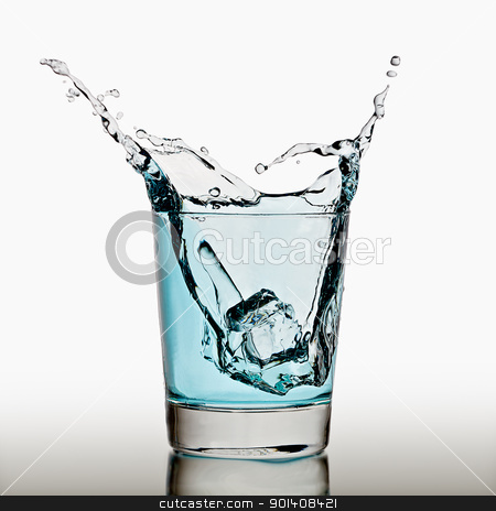 Ice cubes splashing into glass of water stock photo, Ice cube splashing in a cool glass of water by Gert Lavsen