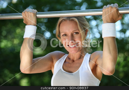 Blond woman exercising on pull-up bar outdoors stock photo, Blond woman exercising on pull-up bar outdoors by photography33