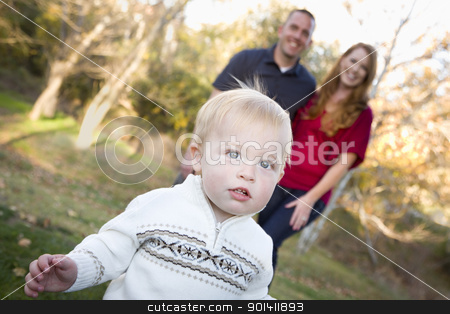 Cute Young Boy Walking as Parents Look On From Behind stock photo, Cute Young Boy Walking in the park as Adoring Parents Look On From Behind. by Andy Dean