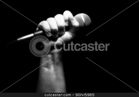 Grayscale Microphone in Fist stock photo, Grayscale Microphone Clinched Firmly in Male Fist on a Black Background. by Andy Dean