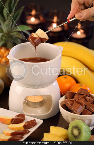 Chocolate fondue stock photo, Photo of bananas being dipped into the bowl of the chocolate fondue. Selective focus on the bananas. by © Ron Sumners