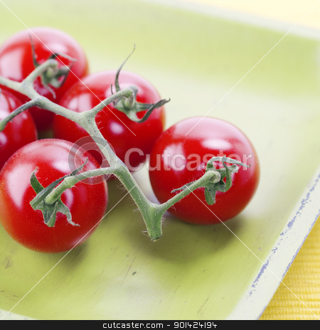 cherry tomatoes stock photo, branch of organic cherry tomatoes on old green plate   by klenova