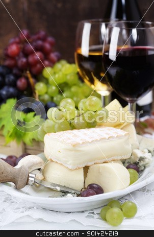 wine and cheese stock photo, Grape and cheese with a bottle and glasses of red and white wine by klenova
