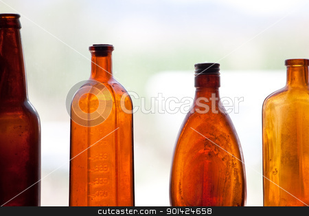 Antique Bottles stock photo, Brown Antique Bottles in window, vintage bottles by Bryan Mullennix