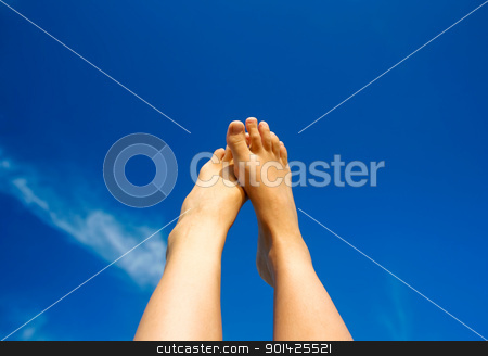 feet in the sky stock photo, the lifted feet of a young woman on a blue sky background by Paul Prescott