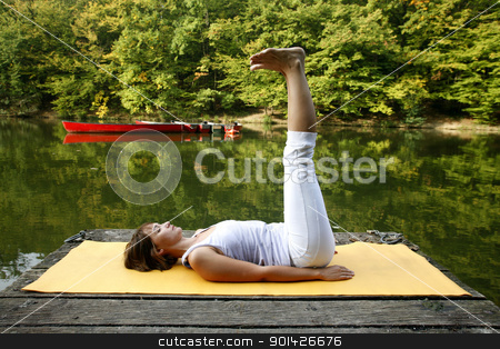 yoga stock photo, Woman doing yoga on lake in park in autumn by Paul Prescott