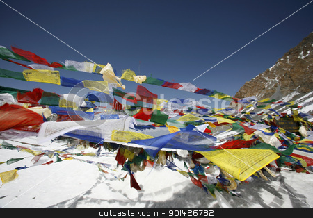 Praying flags stock photo, Tibetan praying flags floating on the Thorong-la pass at 5416m by Paul Prescott