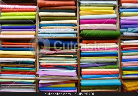 Folded fabrics stock photo, Colourful fabrics folded on shelves in shop interior in Delhi, India. by Paul Prescott