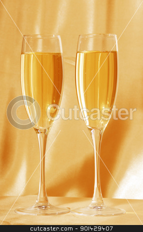 Two glasses of champagne stock photo, Two glasses of champagne against golden background   by sutike