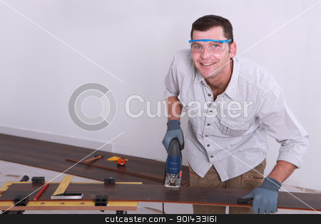 Man cutting tongue and groove floorboards with a jigsaw stock photo, Man cutting tongue and groove floorboards with a jigsaw by photography33