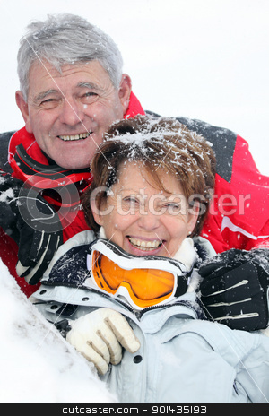 Portrait of a mature couple covered with snowflakes stock photo, Portrait of a mature couple covered with snowflakes by photography33