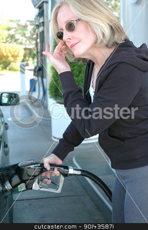 Female pumping gasoline. stock photo, Female beauty pumping gasoline into her car at the service station. by OSCAR Williams