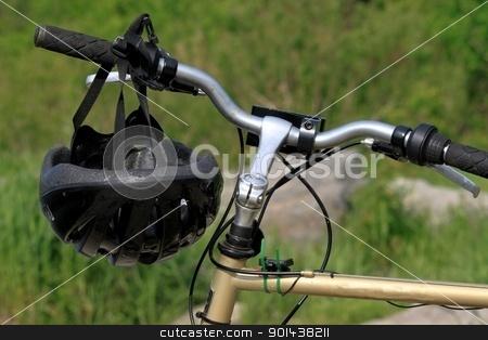 Bike helmet stock photo, Bike helmet hanging on bicycle handle bar by Denis Brien