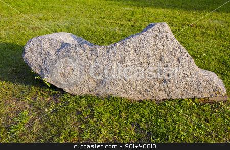 Large decorative stone on grass illuminated by sun stock photo, Large decorative stone on the grass in the garden illuminated by the sun. by sauletas