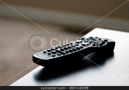Remote Control stock photo, A remote control sitting on table in a living room.  by Chris Hill