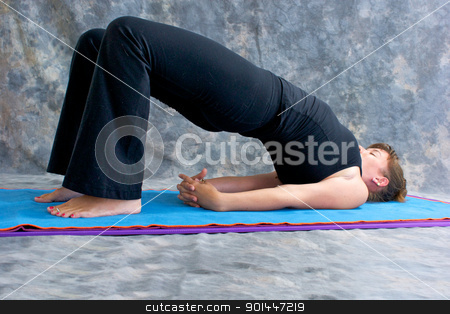 woman doing yoga exercise on mat in Setu Bandhasanasana or bridg stock photo, an athletic brown haired woman is doing yoga exercise  Setu Bandhasanasana or bridge pose on in studio against mottled background. by Stephen Orsillo