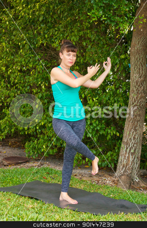 woman doing Yoga pose dancing shiva outdoors on grass stock photo, Young woman on yoga mat outdoors on the grass with trees in the  background in early morning light in dancing shiva posture by Stephen Orsillo