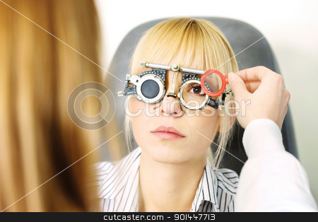 optometrist stock photo, Blond female patient on medical attendance at the optometrist, wearing trial frame for eye testing by iMarin
