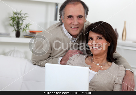 Middle-aged couple with laptop stock photo, Middle-aged couple with laptop by photography33
